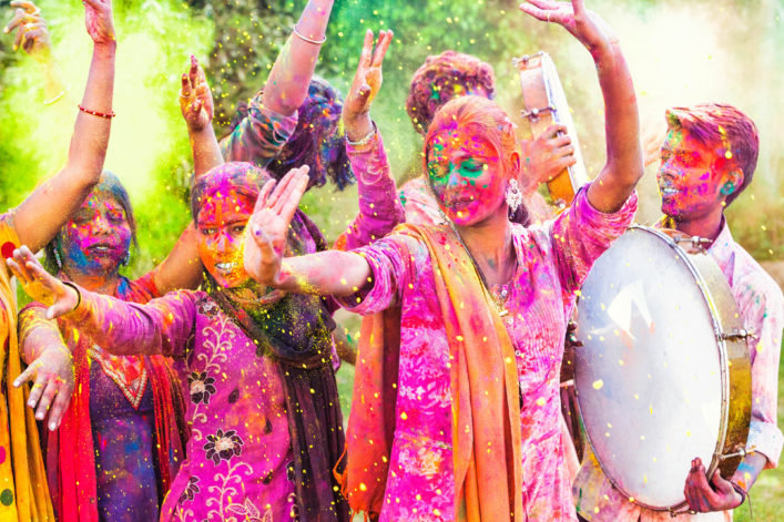 Group of young Indian friends covered in colored dye celebrating Holi festival in Jaipur, India.